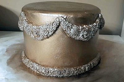 gold cake with floral swags
