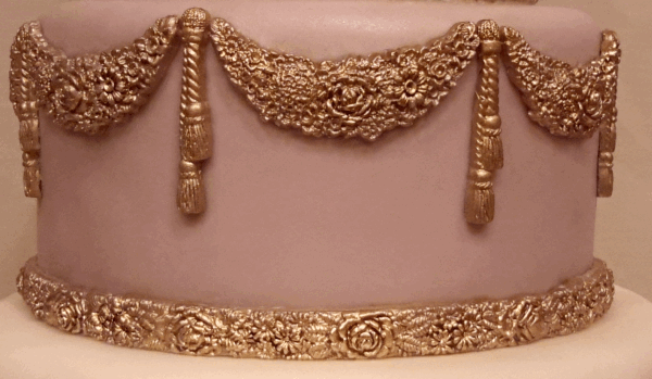 mauve cake with gold swags and tassels